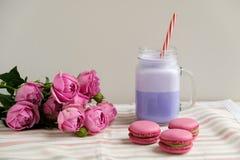在风格化金属螺盖玻璃瓶杯子的紫色咖啡有macarons的和玫瑰和五颜六色的装饰 蓝莓奶昔 独角兽咖啡 库存照片