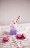 在风格化金属螺盖玻璃瓶杯子的紫色咖啡有macarons的和玫瑰和五颜六色的装饰 蓝莓奶昔 独角兽咖啡 免版税库存照片