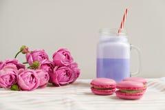 在风格化金属螺盖玻璃瓶杯子的紫色咖啡有macarons的和玫瑰和五颜六色的装饰 蓝莓奶昔 独角兽咖啡 免版税库存图片