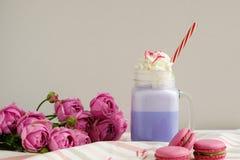 在风格化金属螺盖玻璃瓶杯子的紫色咖啡有macarons的和玫瑰和五颜六色的装饰 蓝莓奶昔 独角兽咖啡 库存图片