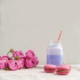 在风格化金属螺盖玻璃瓶杯子的紫色咖啡有macarons的和玫瑰和五颜六色的装饰 蓝莓奶昔 库存图片