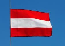 在风的奥地利旗子反对天空 库存图片
