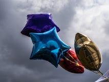 在风的星状箔气球反对灰色天空 免版税图库摄影