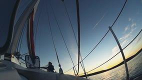 在风的游艇航行在日落 美丽的花费在开阔水域的新婚佳偶夫妇、新娘和新郎时间 股票录像