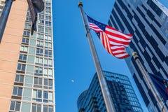 在风的美国国旗波浪,在摩天大楼中在街市布鲁克林,NY,美国 免版税库存照片