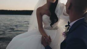 在风的年轻美好的新娘和新郎航行 愉快的新婚佳偶在船上游艇和谈话坐日落 影视素材