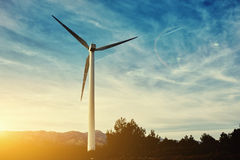 在风车后的美好的日落在领域,反对多云天空背景的电发电器与拷贝空间, 免版税库存图片