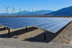在风轮机和mountians前面的太阳电池板 免版税库存照片