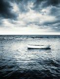 在风雨如磐的云彩下的白色木渔船 免版税库存照片