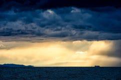 在风雨如磐的云彩的日落横跨反射黑暗和隐约地出现的剧烈的天空的水喜怒无常 库存照片
