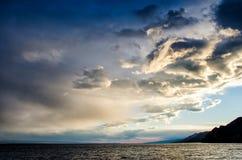 在风雨如磐的云彩的日落横跨反射黑暗和隐约地出现的剧烈的天空的水喜怒无常 库存图片