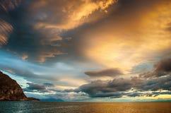 在风雨如磐的云彩的日落横跨反射黑暗和隐约地出现的剧烈的天空的水喜怒无常 免版税库存照片