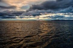 在风雨如磐的云彩的日落横跨反射黑暗和隐约地出现的剧烈的天空的水喜怒无常 免版税库存图片