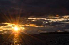 在风雨如磐的云彩的日落横跨反射黑暗和隐约地出现的剧烈的天空的水喜怒无常 免版税图库摄影