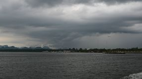 在风雨如磐的云彩的日落横跨水 库存照片
