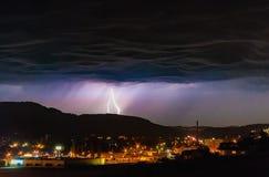 在风雨如磐的夜云彩阴云密布期间,打雷在城市镇的闪电 库存图片