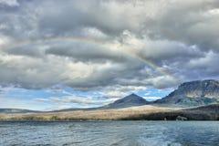 在风雨如磐的天空的彩虹在湖附近的山上 图库摄影