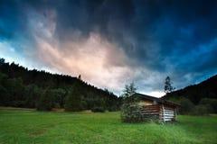 在风雨如磐的日落期间的高山木小屋 免版税库存图片