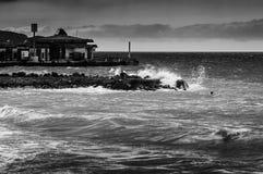 在风雨如磐的海中间的渔夫 免版税库存图片