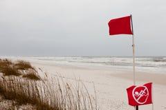 在风雨如磐的海洋沙子海滩的没有游泳旗子 免版税库存照片