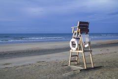 在风雨如磐的海滩的救生员椅子 免版税库存图片