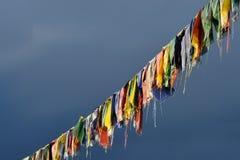 在风雨如磐的蓝天,西藏背景的西藏佛教祷告旗子  免版税图库摄影