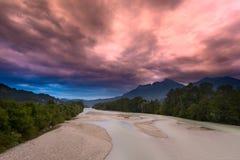 在风暴前的超现实的红色天空在河 免版税库存图片