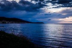 在风暴前的镇静海洋与雨云 免版税库存图片