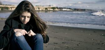 在风暴前面的年轻女性少年在哀伤的海滩 免版税图库摄影