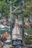 在风暴河的吊桥 免版税库存照片