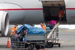 在飞机上的人装载的行李对机场马其顿每r 图库摄影
