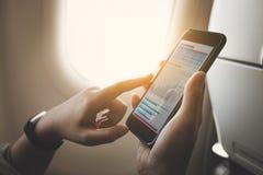 在飞机上的女实业家使用有图表的智能手机在屏幕上 企业技术 免版税库存照片