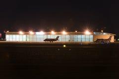 在飞机棚前面停放的私人喷气式飞机在nigt 库存照片