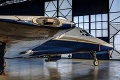 在飞机棚门旁边的小喷气机 免版税库存图片