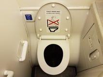 在飞机洗手间盒盖和蓝色充足的按钮的手纸唯一的标志 免版税图库摄影