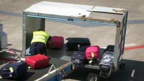 在飞机的机场职员装载的行李 在传送带飞机的行李 影视素材