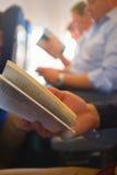 在飞机的阅读书 免版税库存照片