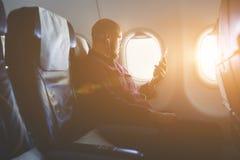 在飞机的飞行期间商人是听的音频书通过手机 免版税库存图片