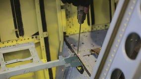 在飞机身体的钻孔在挡板之间的有钻头的 影视素材