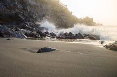 在飞溅在岩石火山的海滩的波浪的日落光 库存照片