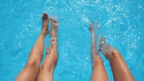 在飞溅在旅馆水池的女性腿的顶视图透明的水  两个朋友坐水池边缘和 影视素材
