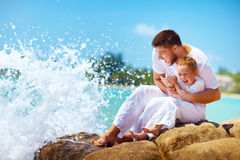 在飞溅愉快的父亲和儿子的水前的片刻 免版税库存图片