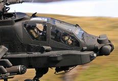 在飞行中军用波音AH-64亚帕基攻击用直升机 库存照片