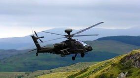 在飞行中军用波音AH-64亚帕基攻击用直升机 库存图片