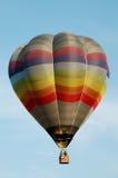 在飞行中多色的镶边热空气气球 免版税图库摄影