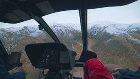 在飞行中直升机的里面看法,当人和飞行员飞行在山 影视素材
