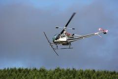 在飞行中飞行员作物喷粉农业直升机的。 图库摄影