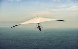在飞行中黄色和白色悬挂式滑翔机与云彩天空 库存图片