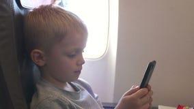 在飞行期间,一个小男孩打在电话的电子游戏在飞机 股票录像
