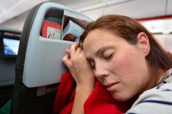 在飞行期间的妇女睡眠 图库摄影